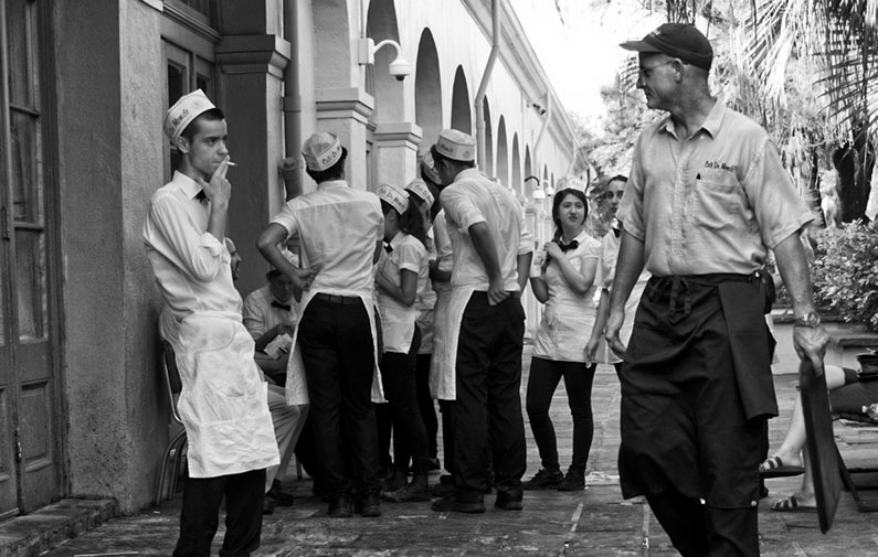 Black and white photo of a unch of workers in hats and aprons taking a smoke break