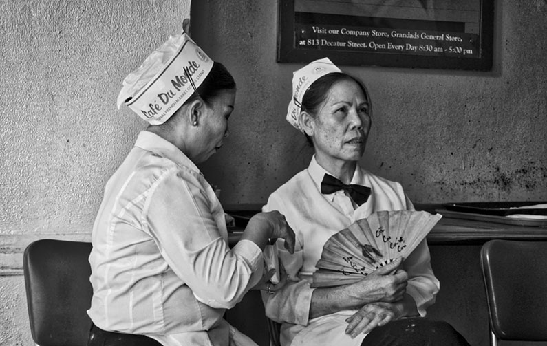 "black and white photo of two women in paper hats reading ""Cafe Du Monde,"" one holding fan"