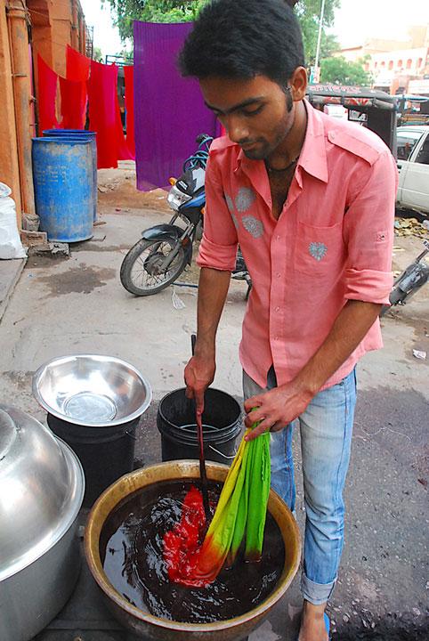 man dying cloth in a bucket