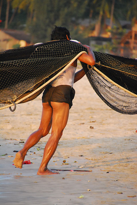 man carrying giant net over his shoulder