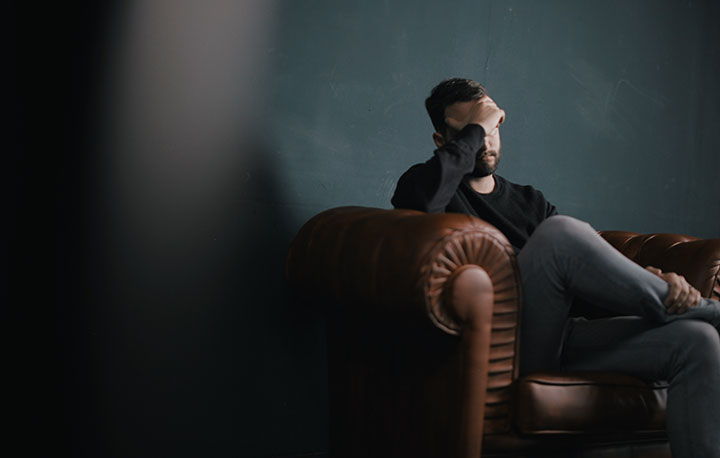 a man holds his head while sitting on a couch