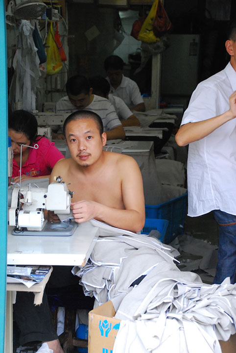man in sweatshop at sewing machine