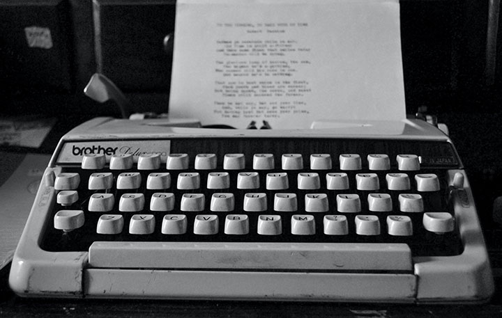 black and white image of typewriter with page of poetry