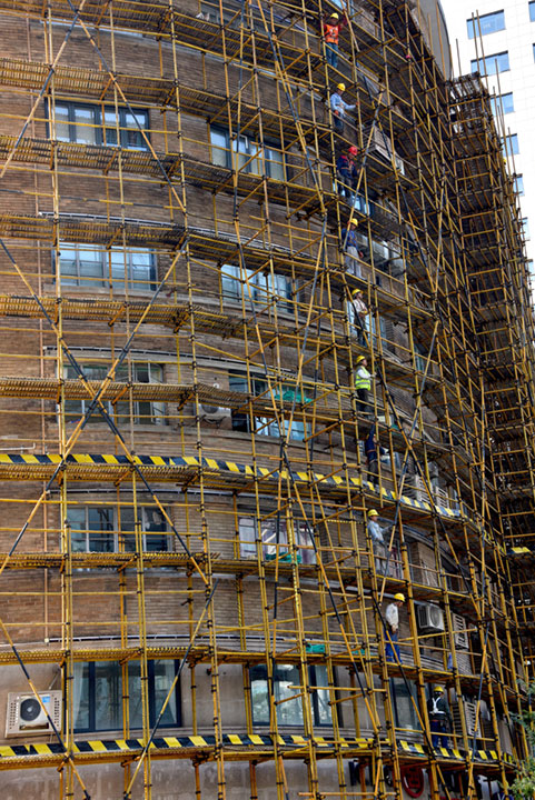workers on scaffolding around a tall building