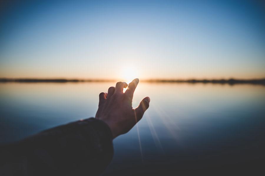 Hand reach toward sunlight over water