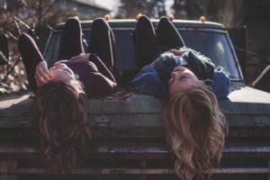 Two women lie on a truck hood