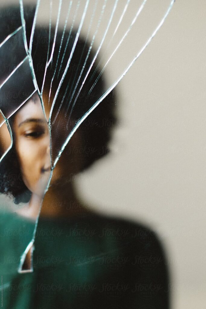 Cracked mirror with warped image of Black woman