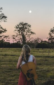 Woman with an acoustic guitar slung over her back facing a moon rise