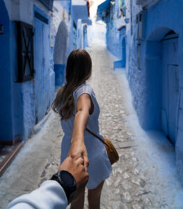 Woman walking down blue corridor leading someone by the hand